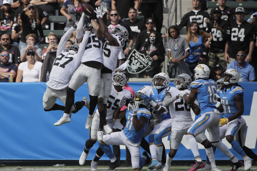 Oakland Raiders defensive back Erik Harris and others battle for an end zone throw during the first half of an NFL football game against the Los Angeles Chargers Sunday, Oct. 7, 2018, in Carson, C ...