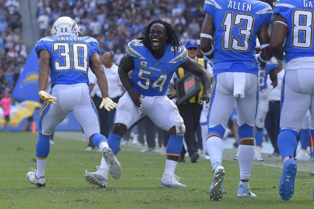 Los Angeles Chargers' Melvin Ingram (54) celebrates with running back Austin Ekeler (30) after Ekeler's touchdown during the first half of an NFL football game against the Oakland Raiders Sunday, ...