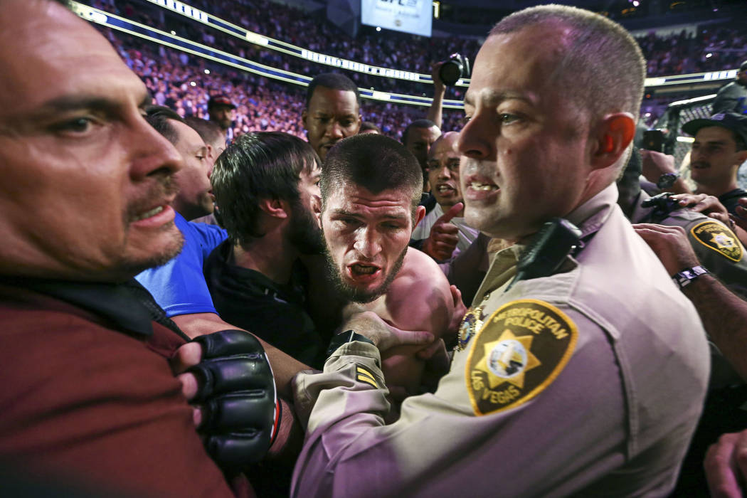 Las Vegas police and security hold back Khabib Nurmagomedov after he defeated Conor McGregor at UFC 229 at T-Mobile Arena in Las Vegas on Saturday, Oct. 6, 2018. Chase Stevens Las Vegas Review-Jou ...