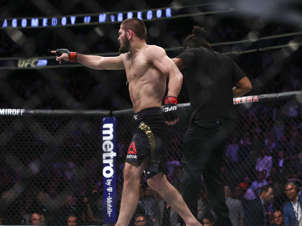Khabib Nurmagomedov points to a member of Conor McGregor's team after he defeated the fighter in their lightweight title bout at UFC 229 at T-Mobile Arena in Las Vegas on Saturday, Oct. 6, 2018. C ...