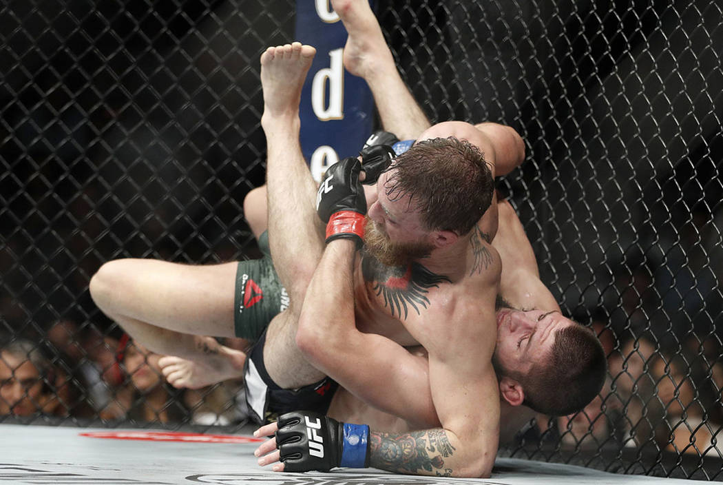 Khabib Nurmagomedov, right, takes down Conor McGregor during a lightweight title mixed martial arts bout at UFC 229 in Las Vegas, Saturday, Oct. 6, 2018. Nurmagomedov won the fight by submission d ...