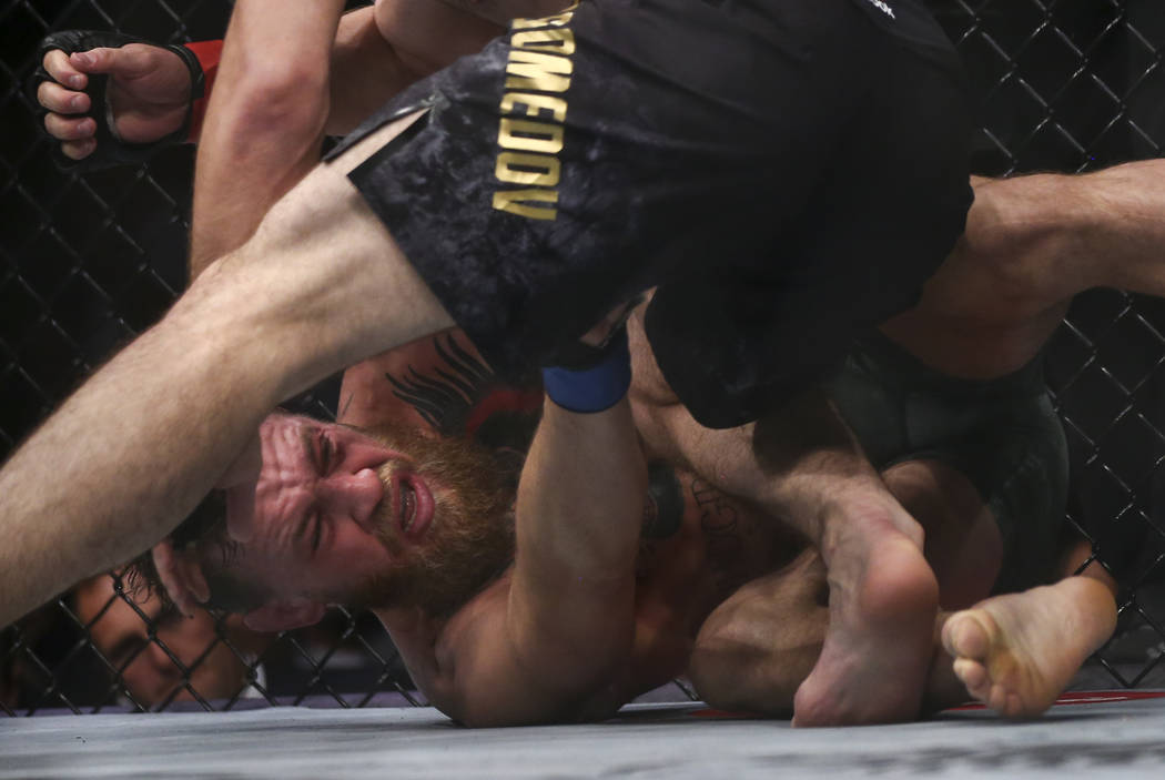 Conor McGregor, left, takes hits from Khabib Nurmagomedov during their lightweight title bout at UFC 229 at T-Mobile Arena in Las Vegas on Saturday, Oct. 6, 2018. Chase Stevens Las Vegas Review-Jo ...