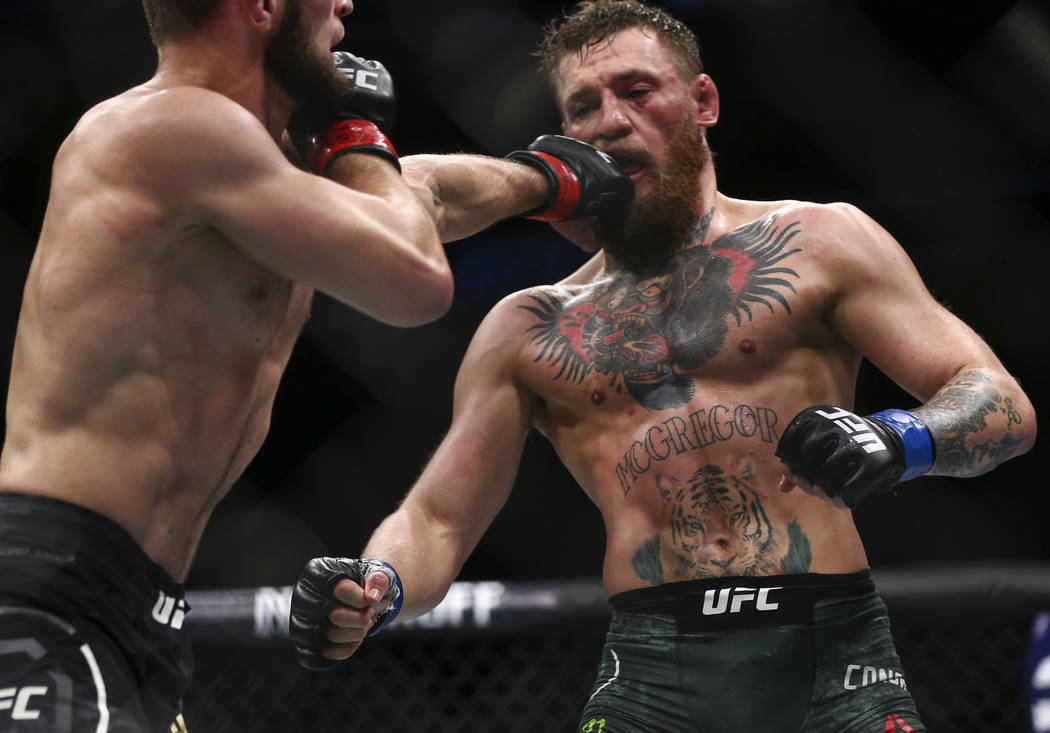 Conor McGregor, right, takes hits from Khabib Nurmagomedov during their lightweight title bout at UFC 229 at T-Mobile Arena in Las Vegas on Saturday, Oct. 6, 2018. Chase Stevens Las Vegas Review-J ...