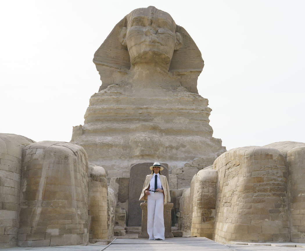 First lady Melania Trump visits the ancient statue of Sphinx, with the body of a lion and a human head, at the historic site of Giza Pyramids in Giza, near Cairo, Egypt, Saturday, Oct. 6, 2018. Fi ...