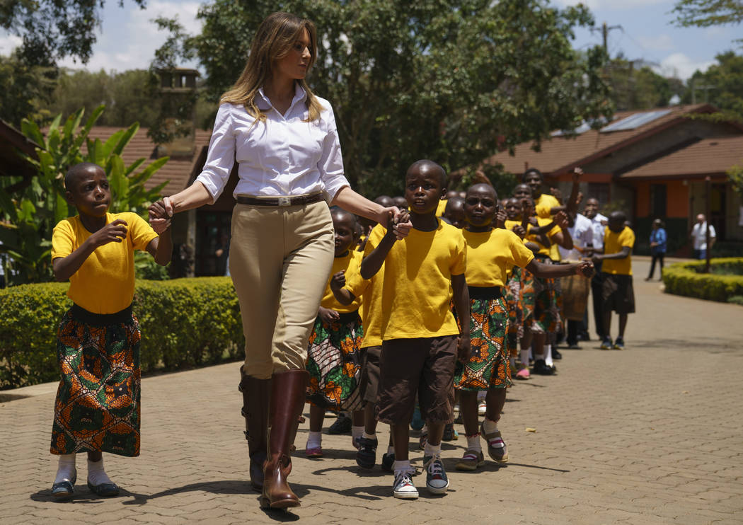 First lady Melania Trump walks with children as she visits the Nest Orphanage in Limuru, Kenya, Friday, Oct. 5, 2018. The first lady is visiting Africa on her first big solo international trip, ai ...