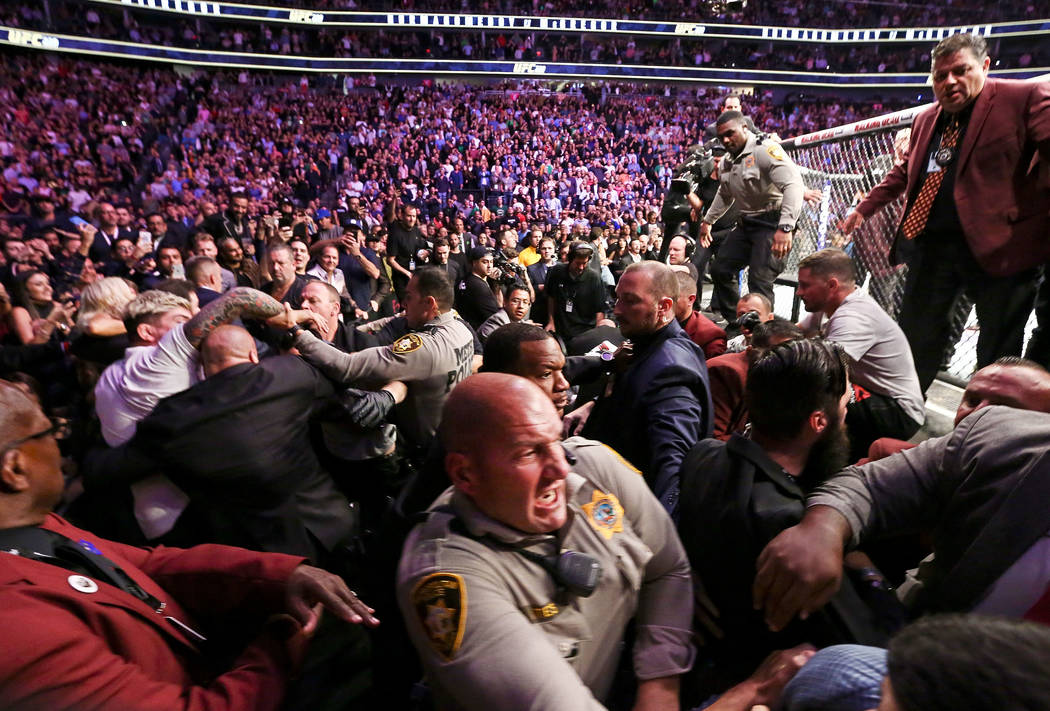 Las Vegas police and security try to stop fights that broke out after Khabib Nurmagomedov jumped out of the octagon following his win over Conor McGregor in their lightweight title bout at UFC 229 ...