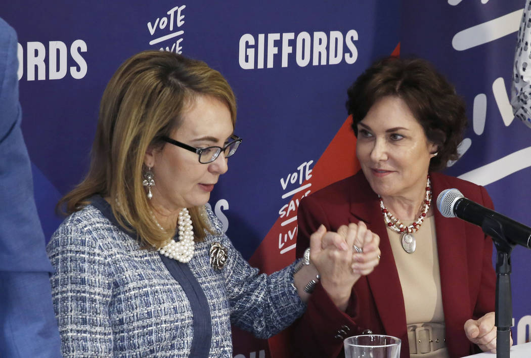 Former Congresswoman Gabby Giffords, left, and U.S. Rep. Jacky Rosen, D-Nev., hold hands prior to the start of a roundtable discussion with gun violence survivors, at UNLV on Tuesday, Oct. 2, 2018 ...