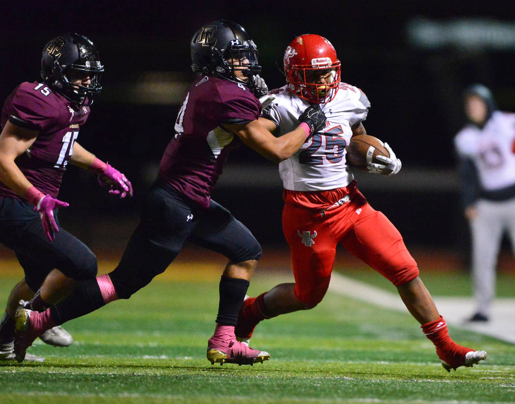 Arbor View running back Kyle Graham (25) battles with Faith Lutherans' Sebastian Burke (4) while running the ball in the second half of a game at Faith Lutheran in Las Vegas on Friday, Oct. 5, 201 ...