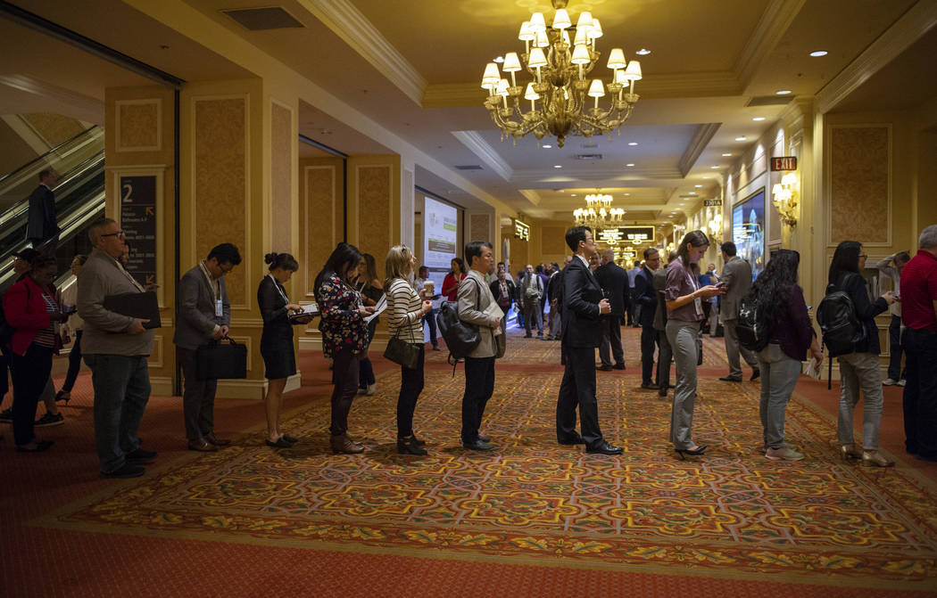 Attendees of the Global Gaming Expo (G2E), hosted by the American Gaming Association, line up as they wait to attend the next panel as the G2E kicks off its first day at the Sands Expo in Las Vega ...