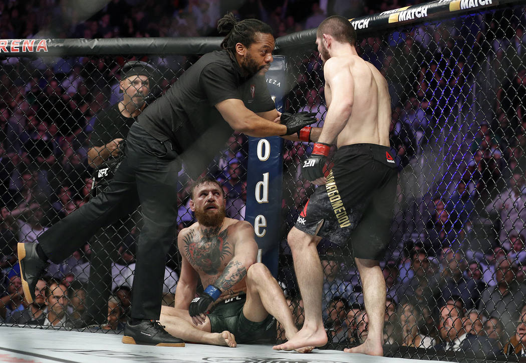 Khabib Nurmagomedov, right, is held back by referee Herb Dean after fighting Conor McGregor, bottom, during a lightweight title mixed martial arts bout at UFC 229 in Las Vegas, Saturday, Oct. 6, 2 ...
