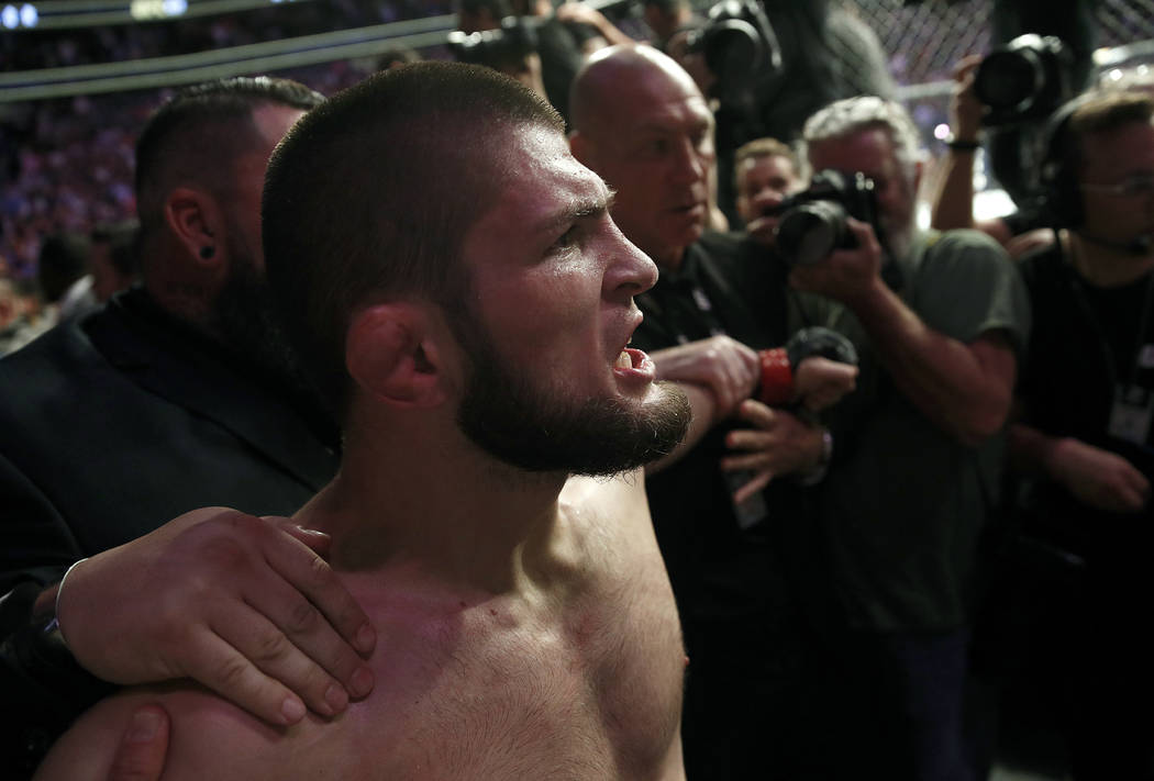 Khabib Nurmagomedov is held back outside of the cage after beating Conor McGregor in a lightweight title mixed martial arts bout at UFC 229 in Las Vegas, Saturday, Oct. 6, 2018. Nurmagomedov won t ...