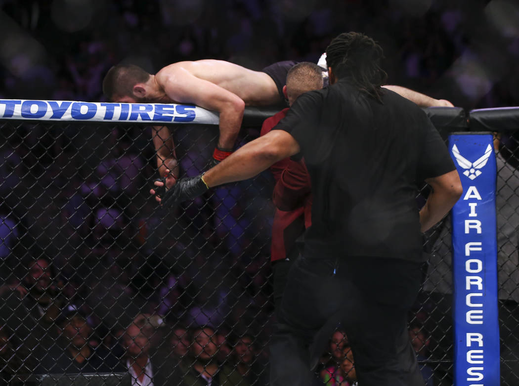 Khabib Nurmagomedov jumps out of the octagon after he defeated the fighter in their lightweight title bout at UFC 229 at T-Mobile Arena in Las Vegas on Saturday, Oct. 6, 2018. Chase Stevens Las Ve ...