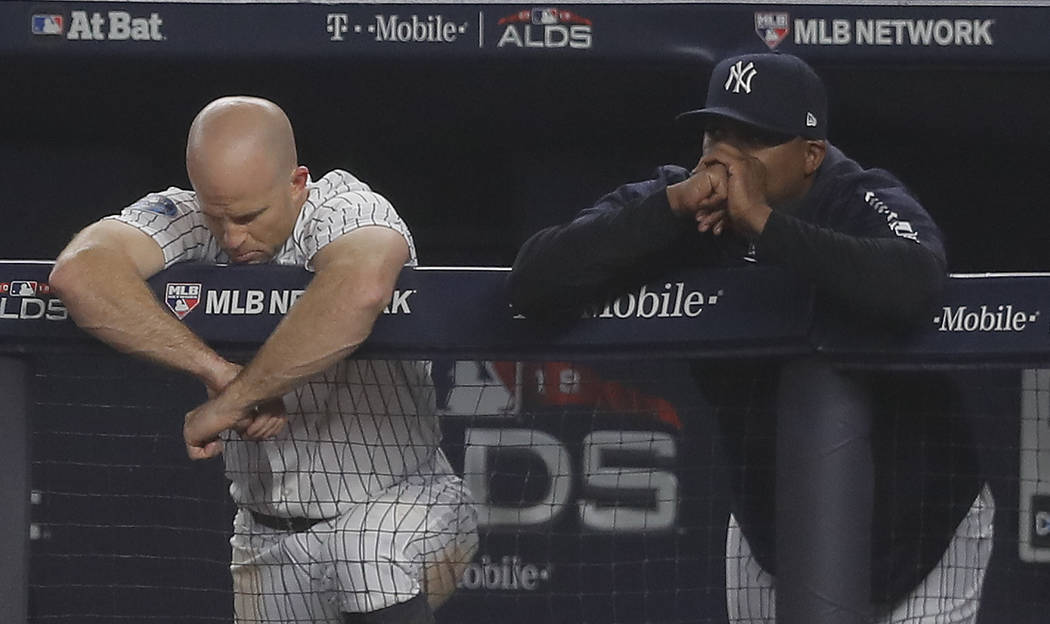 New York Yankees' Brett Gardner, left, and hitting coach Marcus Thames watch play against the Boston Red Sox from the dugout during the eighth inning of Game 3 of baseball's American League Divisi ...