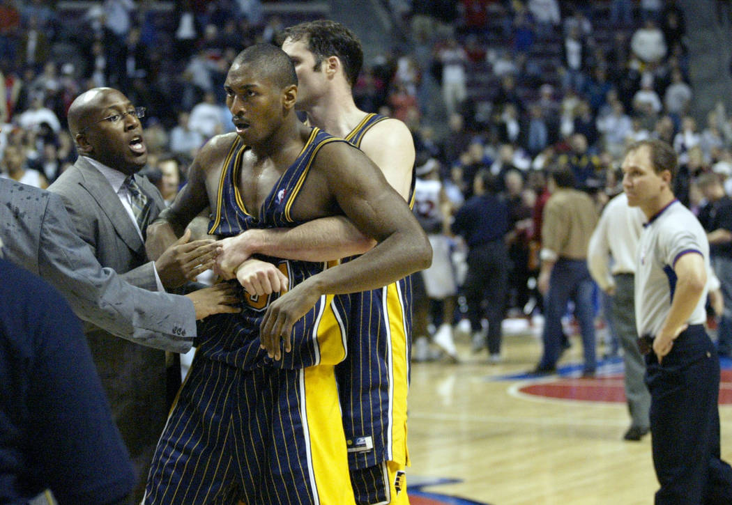 FILE - In this Nov. 19, 2004 file photo, Indiana Pacers' Ron Artest is restrained before being escorted off the court following a fight with the Detroit Pistons and fans in Auburn Hills, Mich. Art ...
