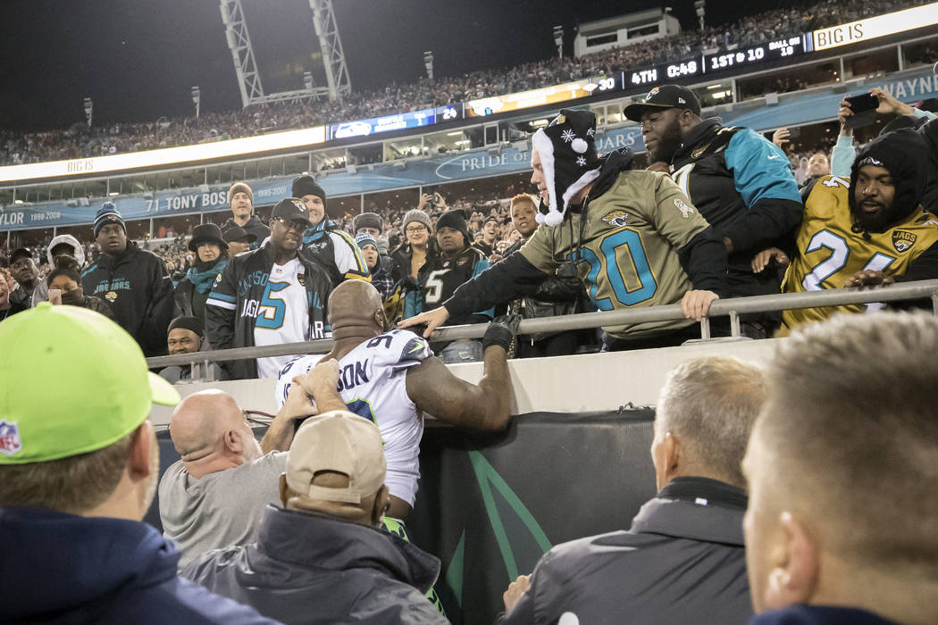 Seattle Seahawks defensive tackle Quinton Jefferson, center, tries to climb up in the stands after Jacksonville Jaguars fans threw objects at him at the end of an NFL football game, Sunday, Dec. 1 ...