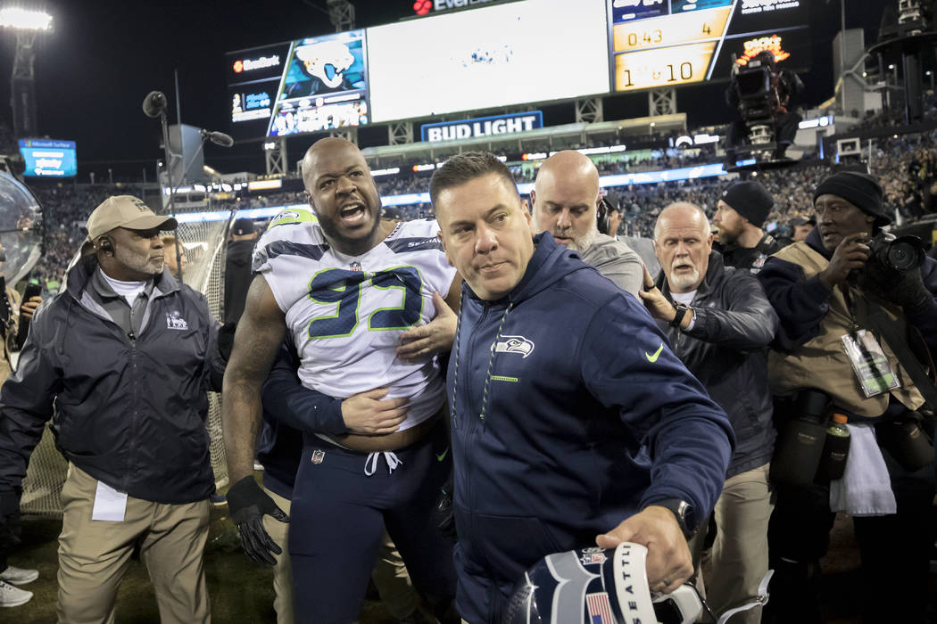 Members of the Seattle Seahawks staff escort Seattle Seahawks defensive tackle Quinton Jefferson (99) from the field after he got into a shouting match with fans, when objects were thrown at him, ...