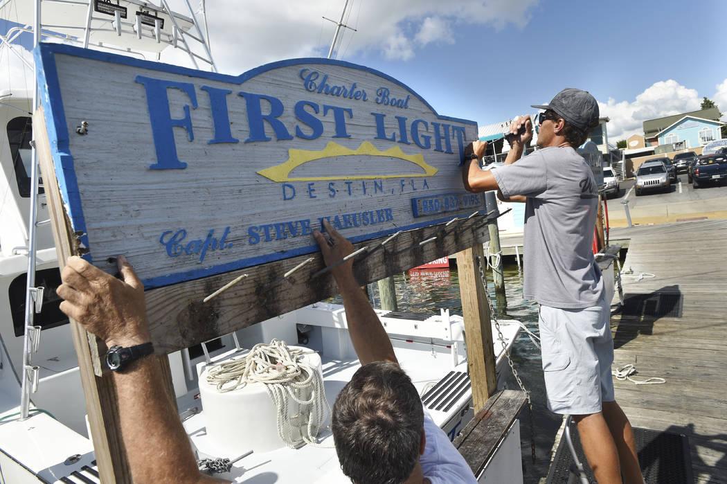 """Capt. Steve Haeusler, left, and Wyatt Ferreira take down the sign for Haeusler's charter fishing boat """"First Light"""" on Monday, Oct. 8, 2018. Boat captains in this fishing community were ..."""