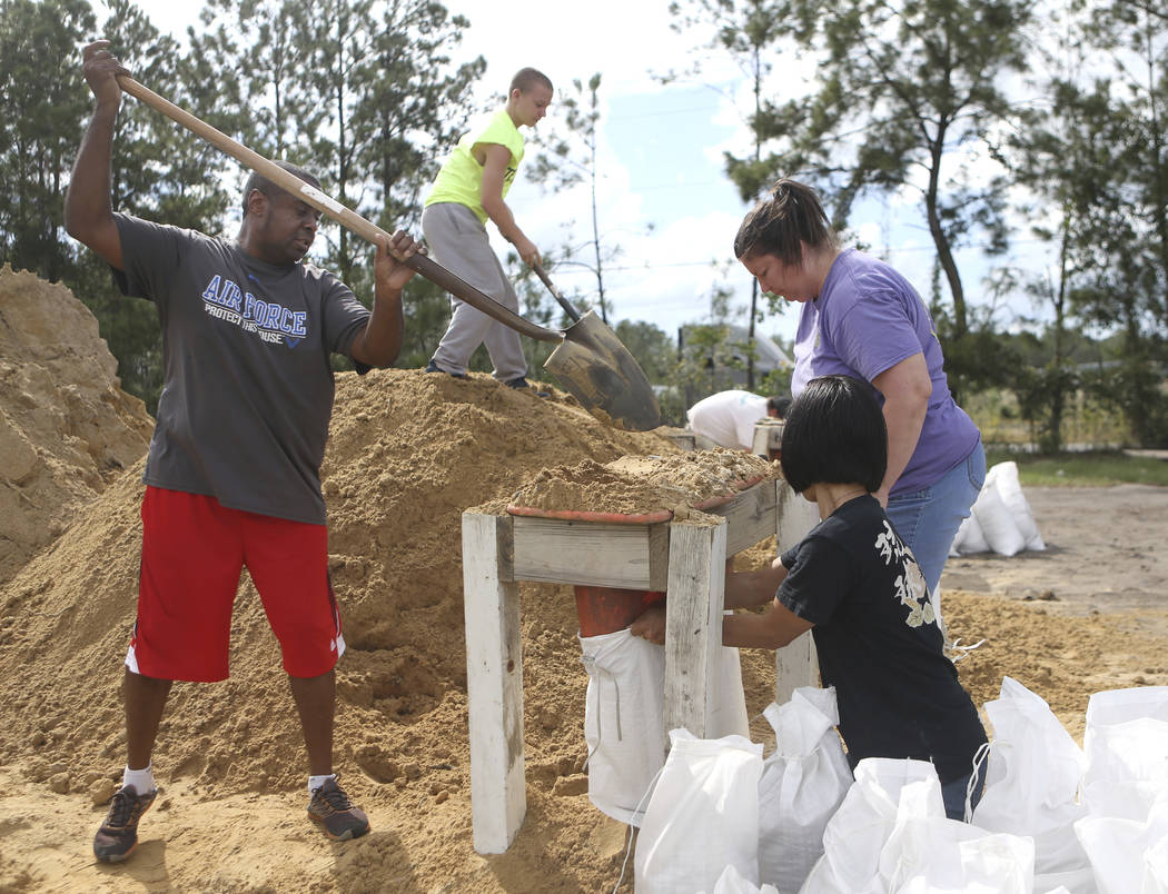 From left, Haskel Johnson, Daniel Tippett, Jennifer Tippett and Nobuko Johnson fill sand bags at the Lynn Haven Sports Complex in Lynn Haven, Fla., Monday, Oct. 8, 2018, to prepare for Hurricane M ...