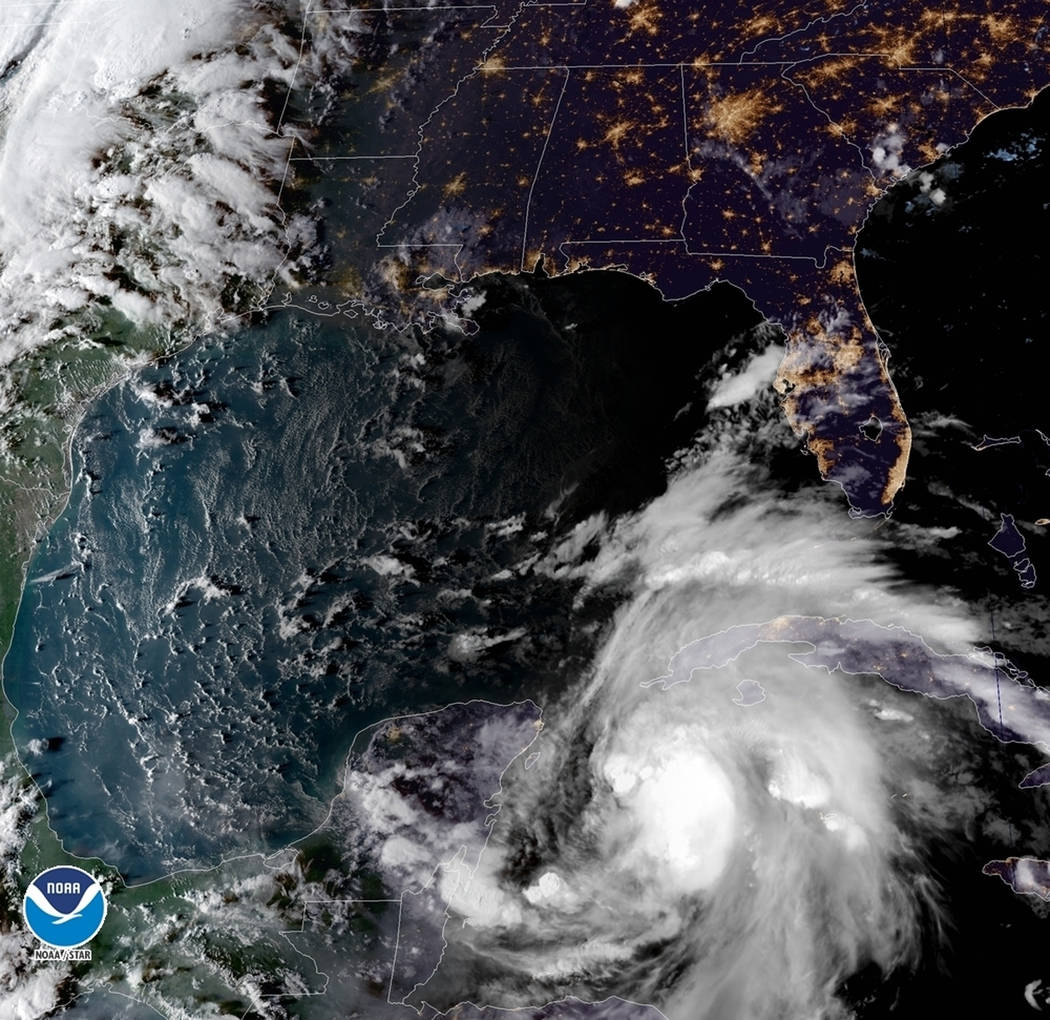 This satellite image provided by the National Oceanic and Atmospheric Administration shows a view of Tropical Storm Michael, lower right, churning as it heads toward the Florida Panhandle, Sunday, ...