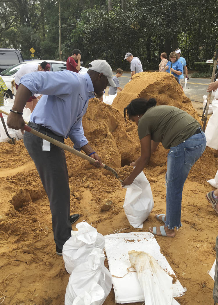 Tallahassee Mayor and Democratic gubernatorial candidate, Andrew Gillum, left, helps Eboni Sipling fill up sandbags in Tallahassee, Fla., Monday, Oct. 8, 2018. Residents in Florida's Panhandle and ...