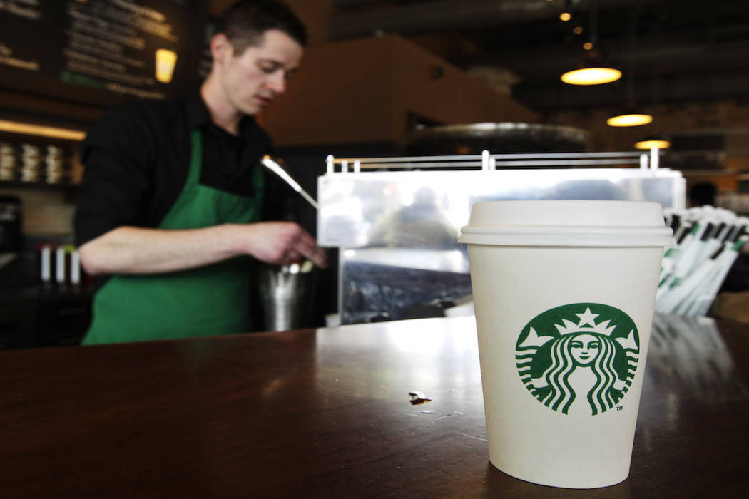 A Starbucks drink waits for a customer to pick it up as barista Josh Barrow prepares another at left, Friday, April 27, 2012, in Seattle. (AP Photo/Ted S. Warren)