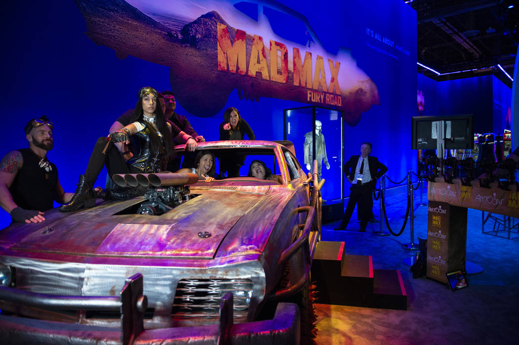 Attendees pose with Mad Max themed car at the Aristocrat booth at the 18th annual Global Gaming Expo at Sands Expo and Convention Center in Las Vegas, Tuesday, Oct. 9, 2018. Caroline Brehman/Las V ...