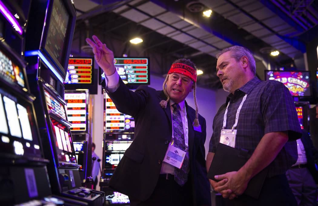 Danny Ouellette, left, shows off a Willie Nelson themed slot machine to attendee Ray Moody at the 18th annual Global Gaming Expo at Sands Expo and Convention Center in Las Vegas, Tuesday, Oct. 9, ...