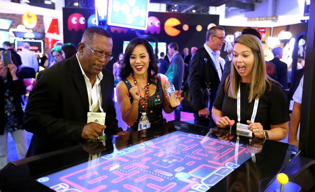 Nikki Tuazon in the Gamblit Gaming booth, center, helps Vernon Finch, a commission member with Virgin Islands Lottery, and Sara Tait, executive director of Indiana Gaming Commission play Pac-Man s ...