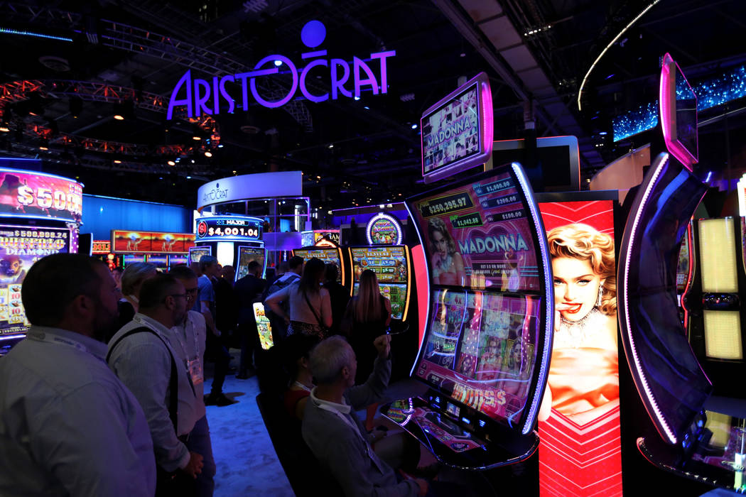 Conventioneers play the Madonna slot machine at the Aristocrat booth at the 18th annual Global Gaming Expo at Sands Expo and Convention Center in Las Vegas Tuesday, Oct. 9, 2018. G2E runs through ...