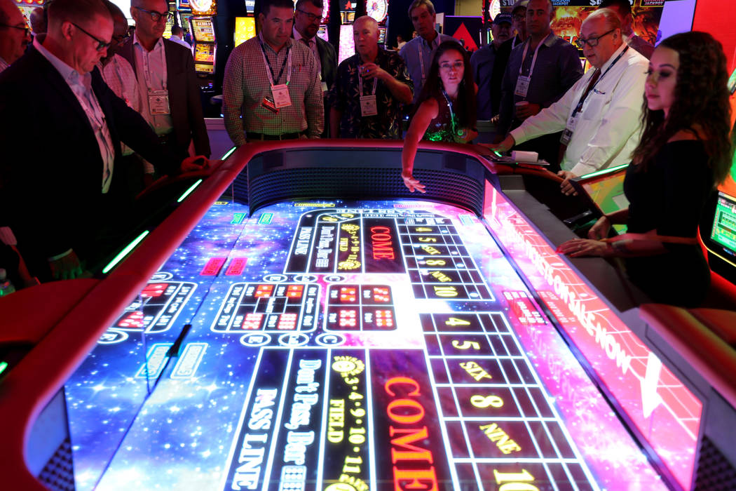 Tifany Tinnin, a slot technician at Mazatzal hotel-casino in Payson, Ariz., rolls the dice on an electronic craps table in the Aruze Gaming booth at the 18th annual Global Gaming Expo at Sands Exp ...