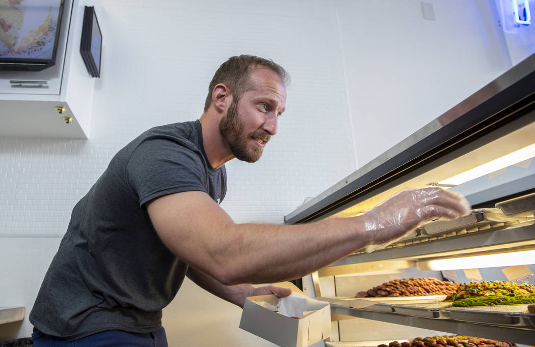 Max Jacobson-Fried, owner of Freed's Bakery, reaches for a cookie to box up in Freed's newest location at 6475 N. Decatur Blvd. in the Shadow Mountain Marketplace, just north of the northern 215 B ...