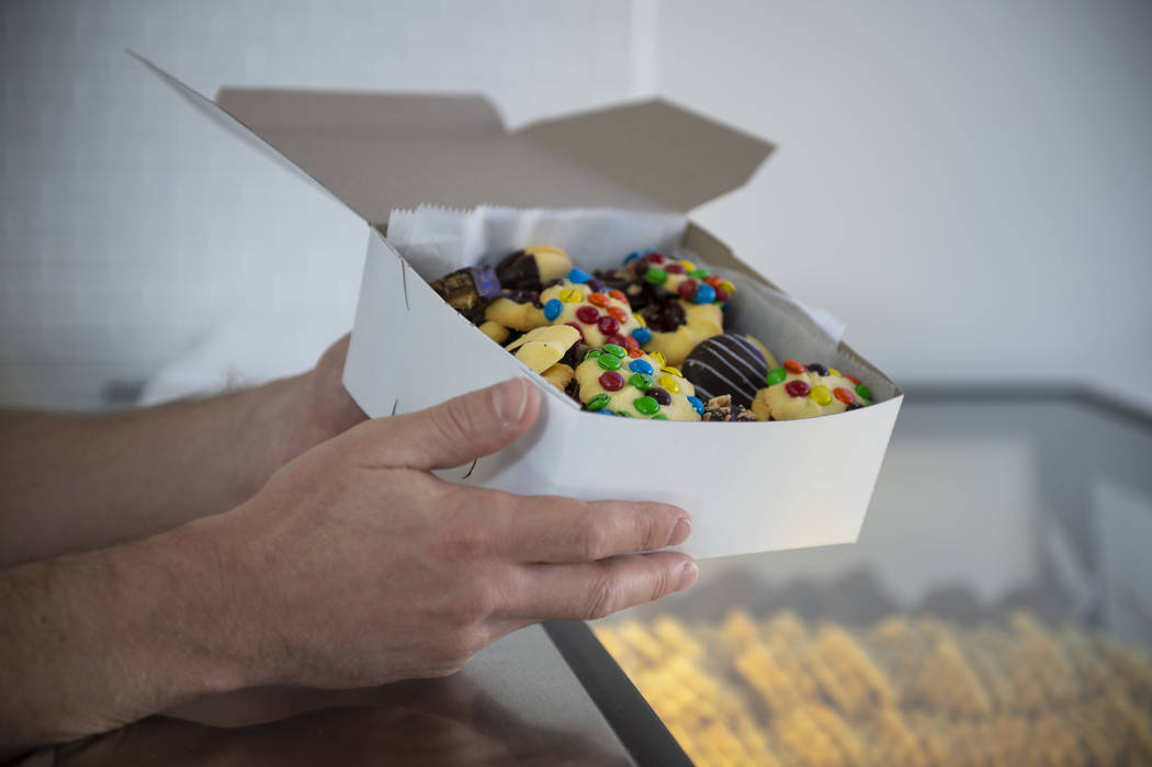 Max Jacobson-Fried, owner of Freed's Bakery, holds a box of various sweet treats in Freed's newest location at 6475 N. Decatur Blvd. in the Shadow Mountain Marketplace, just north of the northern ...