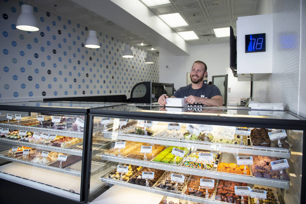 Max Jacobson-Fried, owner of Freed's Bakery, smiles behind the counter with a box full of various sweet treats in Freed's newest location at 6475 N. Decatur Blvd. in the Shadow Mountain Marketplac ...
