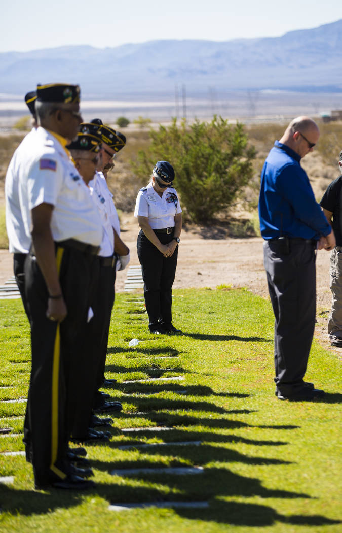 Bobi Oates, a retired Air Force senior master sergeant and member of Women Veterans of Nevada, center, bows her head during the Missing in Nevada ceremony held at the Southern Nevada Veterans Memo ...