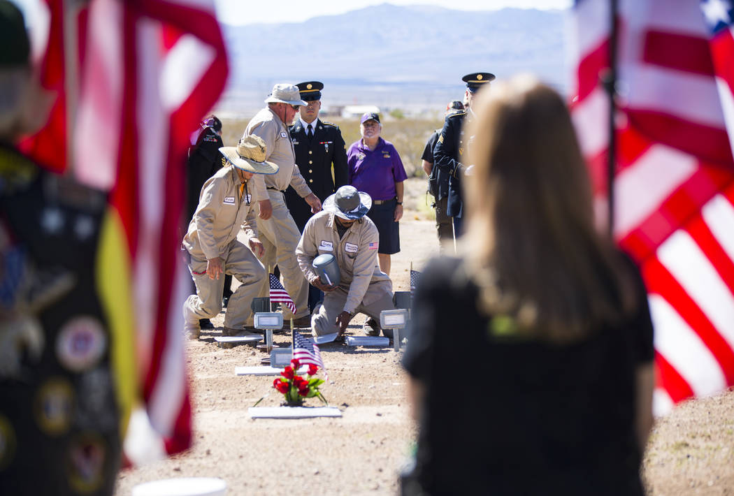 The remains of 12 veterans and one spouse, including, including Navy veteran Raymond Reed, who passed away in 1986 and served in the Korean and Vietnam wars, seen in the urn, center, are honorably ...