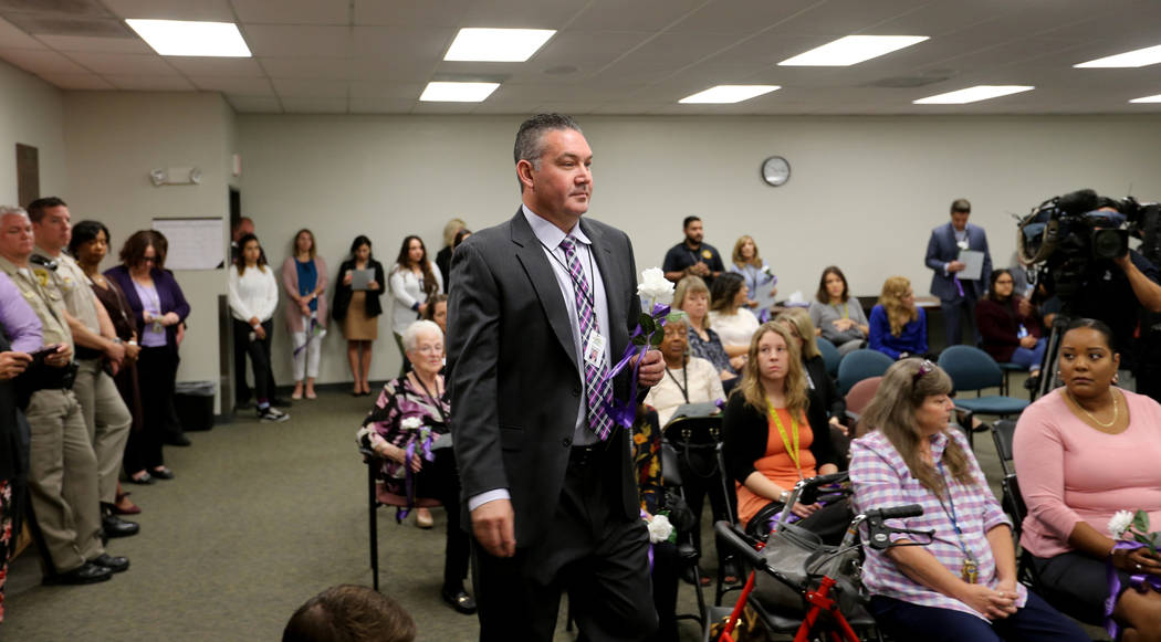 Capt. Sean Thoman prepares to place a rose during a Community Coalition for Victims Rights and Metropolitan Police Department ceremony at the Southern Nevada Family Justice Center in Las Vegas Thu ...