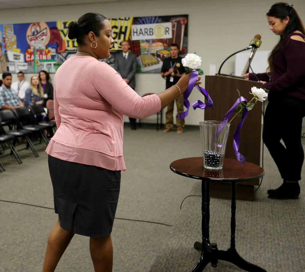 Yamille Muriel places a rose during a Community Coalition for Victims Rights and Metropolitan Police Department ceremony at the Southern Nevada Family Justice Center in Las Vegas on Thursday, Oct. ...