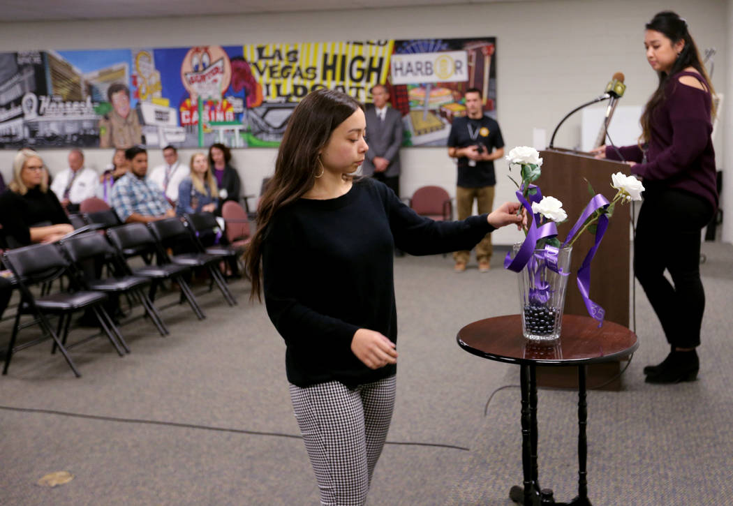 UNLV student Kim Yoder places a rose during a Community Coalition for Victims Rights and Metropolitan Police Department ceremony at the Southern Nevada Family Justice Center in Las Vegas on Thursd ...