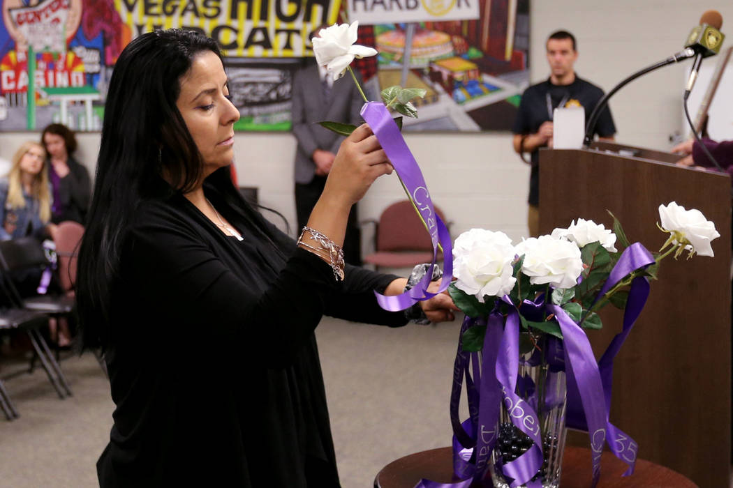 Nancy Hernandez of Safe Nest places a rose during a Community Coalition for Victims Rights and Metropolitan Police Department ceremony at the Southern Nevada Family Justice Center in Las Vegas on ...
