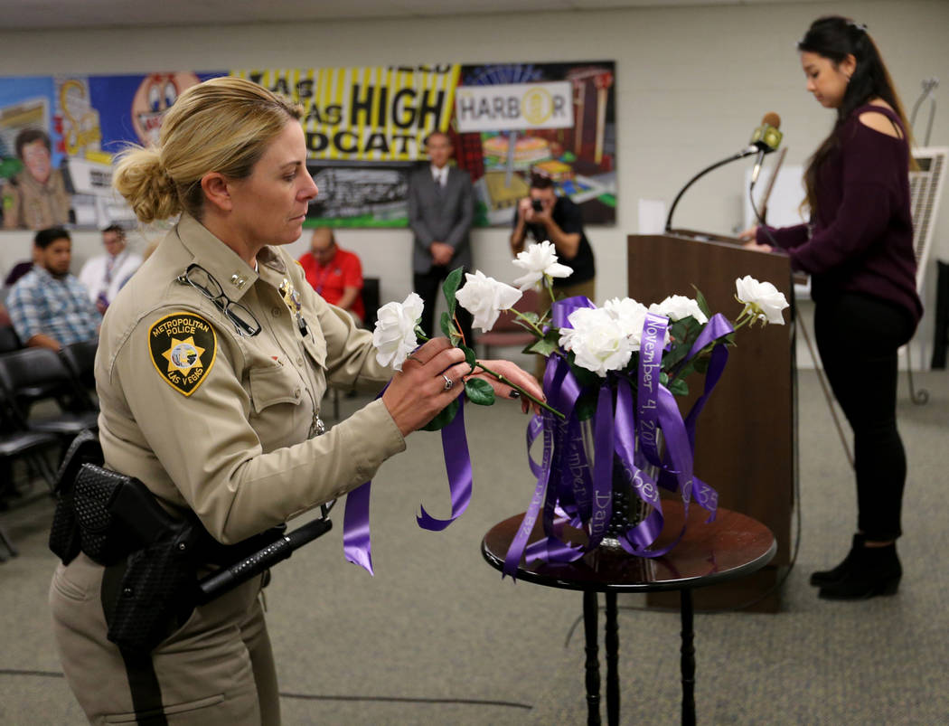 Capt. Kelly McMahill places a rose during a Community Coalition for Victims Rights and Metropolitan Police Department ceremony at the Southern Nevada Family Justice Center in Las Vegas on Thursday ...