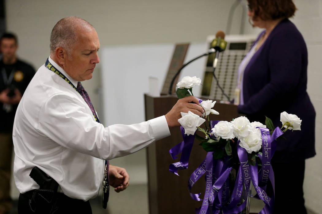 Detective Matt Campbell places a rose during a Community Coalition for VictimÕs Rights and Metropolitan Police Department ceremony at the Southern Nevada Family Justice Center in Las Vegas Th ...