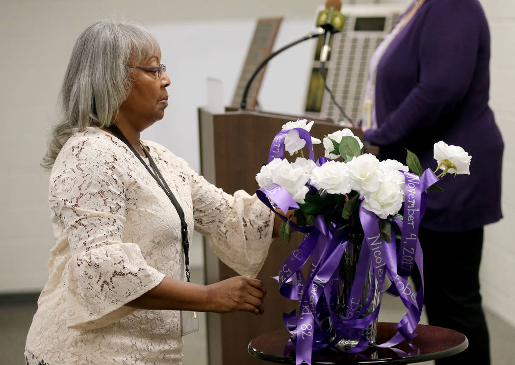 Las Vegas police support technician Lillian Sherman places a rose during a Community Coalition for VictimÕs Rights and Metropolitan Police Department ceremony at the Southern Nevada Family Ju ...