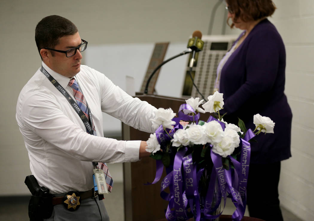 Sgt. Blake Smith places a rose during a Community Coalition for VictimÕs Rights and Metropolitan Police Department ceremony at the Southern Nevada Family Justice Center in Las Vegas Thursday, ...