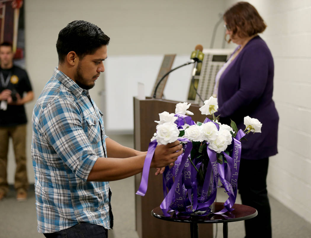 Luis Fregoso-Aguirre, a victim advocate at Nellis Air Force Base, places a rose during a Community Coalition for VictimÕs Rights and Metropolitan Police Department ceremony at the Southern Ne ...