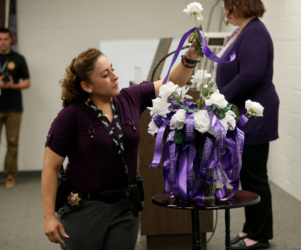Detective S. Salazar places a rose during a Community Coalition for VictimÕs Rights and Metropolitan Police Department ceremony at the Southern Nevada Family Justice Center in Las Vegas Thurs ...