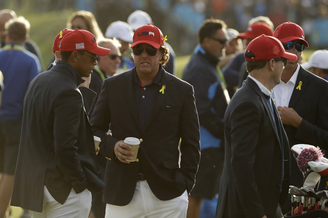 Tiger Woods of the US, left, and Phil Mickelson of the US wait for the closing ceremony after Europe won the Ryder Cup on the final day of the 42nd Ryder Cup at Le Golf National in Saint-Quentin-e ...