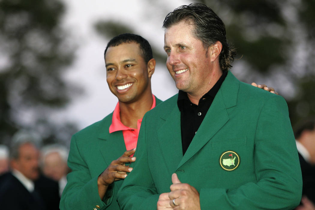 Phil Mickelson, right, gets his Masters Green Jacket from last years champion Tiger Woods after winning the 2006 Masters golf tournament at the Augusta National Golf Club in Augusta, Ga., Sunday, ...