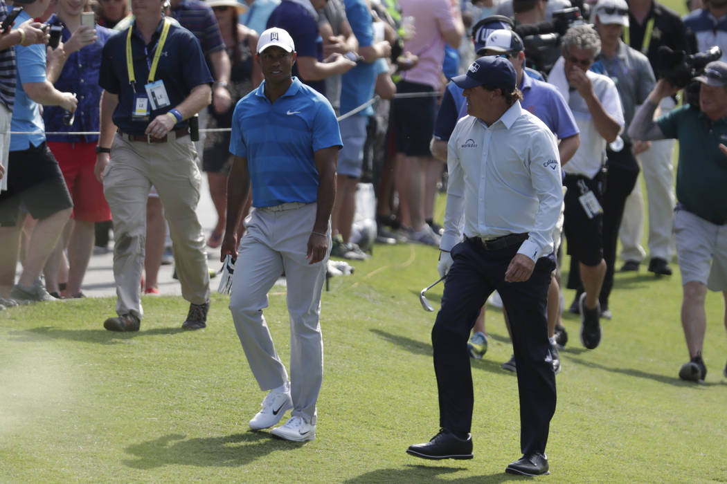 Tiger Woods, left, and Phil Mickelson, right, walks down the 10th fairway during the first round of the Players Championship golf tournament, Thursday, May 10, 2018, in Ponte Vedra Beach, Fla. (AP ...