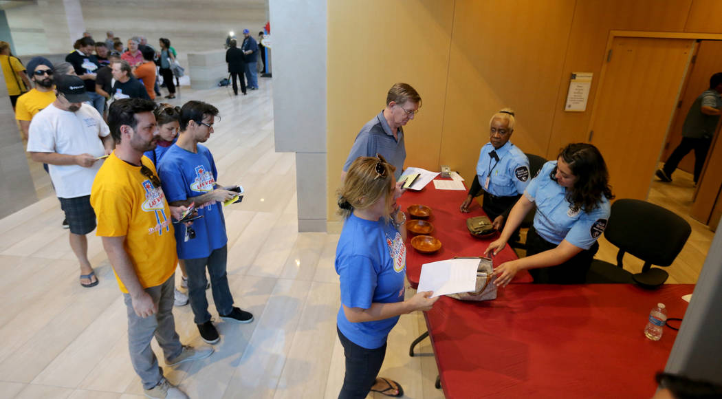 People go through security screening before a Las Vegas Planning Commission meeting to discuss a proposal to stop licensing short-term rentals within the City of Las Vegas during a meeting at City ...