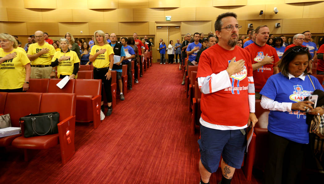People who are for a proposal to stop licensing short-term rentals, left, and those against the proposal, right, say the Pledge of Allegiance before a Las Vegas Planning Commission meeting at City ...